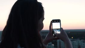 Girl makes a photo from the roof.  stock video footage