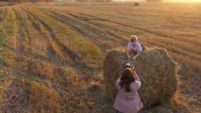 The girl makes the photo and video of teen lain on the haystack. stock video