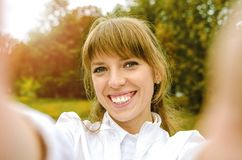 The girl makes a portrait selfie Stock Images