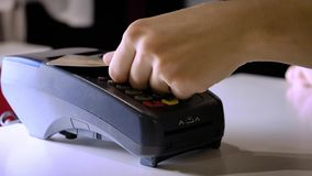 A girl makes a purchase with a bank or credit card using an electronic chip in the card. Insert a card into the terminal. Of a non-cash payment stock footage
