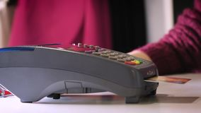 A girl makes a purchase with a bank or credit card using an electronic chip in the card. Insert a card into the terminal. Of a non-cash payment stock video footage