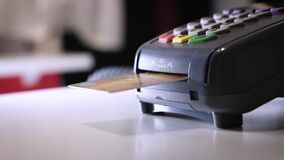 A girl makes a purchase with a bank or credit card using an electronic chip in the card. Insert a card into the terminal