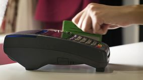 A girl makes a purchase with a bank or credit card using magnetic tape. A girl makes a purchase with a bank or credit card using magnetic tape stock video footage