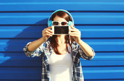 Girl makes self-portrait on smartphone and listens to music in headphones, screen phone Stock Photo