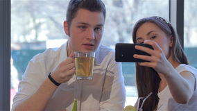 Girl makes a selfie with her boyfriend. Attractive girl making selfie with her handsome boyfriend. Caucasian man drinking his tea while his pretty girl stock footage