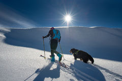 Girl makes ski mountaineering with his dog. In the sun Stock Photos
