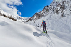 Girl makes ski mountaineering uphill alone. In the alps Stock Photo