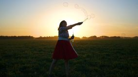 Girl makes soap bubbles at sunset stock video