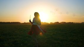 Girl makes soap bubbles at sunset stock footage
