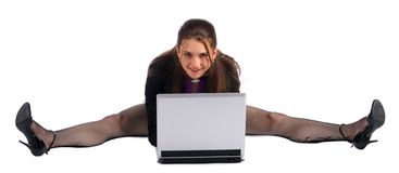 Girl makes splits with notebook on floor. Royalty Free Stock Images