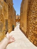 Girl makes a welcome guesture on old narrow street of Victoria, Malta stock photos