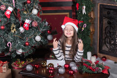 Girl makes a wish at Christmas. Near tree at home Stock Image