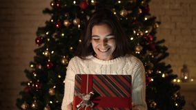 The girl makes a wish and opens a Christmas gift package. the concept of holidays and New year. the girl is happy and