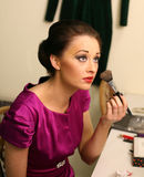 Girl with makeup. Beautiful girl applying makeup with a brush Royalty Free Stock Images