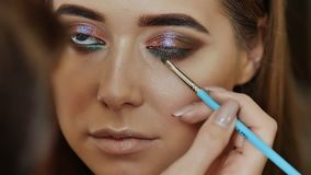 Girl makeup artist paints the eyes of the girl model. Stroke for the lower eyelids. stock footage