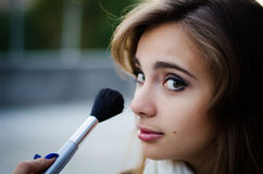 Girl with makeup brush Stock Image