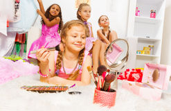 Girl makeup with brush and her friends behind Royalty Free Stock Photos