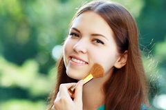Girl with makeup brush Stock Photo