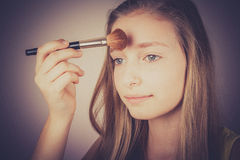 Girl makeup brush trying to conceal, grain effect Royalty Free Stock Photo
