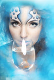 Girl with makeup, with a fish in a glass Stock Photography