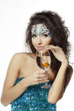 Girl with makeup, with a fish in a glass Royalty Free Stock Photography