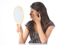 Girl with makeup mirror adjusting her makeup Royalty Free Stock Images