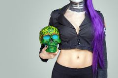 Girl with makeup and purple hair holds a painted skull in her hand on a gray background. Mexican celebration of the Day of the Dea. D Dia de los Muertos and the royalty free stock images