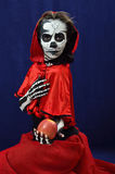 Girl makeup skeleton offering apple. Skeleton Girl in red cape Royalty Free Stock Photos