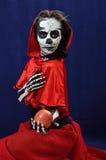 Girl makeup skeleton offering apple Royalty Free Stock Photos