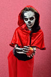 Girl makeup skeleton offering apple. Skeleton Girl in red cape Royalty Free Stock Photo