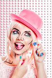 Girl with makeup in style pop art is eating hard candy. Stock Photo