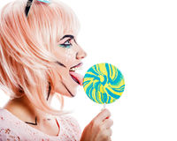 Girl with makeup in the style of pop art and lollipop. Girl with makeup in the style of pop art. A girl holding a lollipop and licking it. The concept of the stock photos