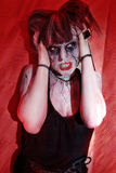 Girl with makeup zombie horror shows. Against backdrop of red wall royalty free stock photography