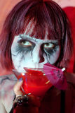 Girl with makeup zombies bloody cocktail drink from glass Stock Images