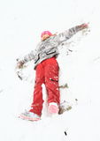 Girl making angel in snow Stock Photo