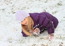 Girl making angel in snow Stock Photos