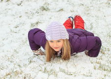Girl making sliding in snow Royalty Free Stock Photography