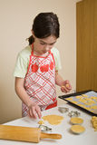 Girl making cakes Stock Images