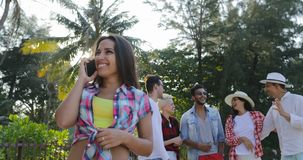 Girl Making Call Using Cell Smart Phone Over Cheerful People Group Talking In Tropical Palm Tree Park. Slow Motion 60 stock video