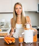 Girl making carrot juice Royalty Free Stock Photo