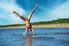 Girl making cartwheel in the water Royalty Free Stock Photo