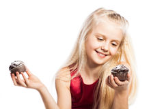 Girl making a choice between two cakes Royalty Free Stock Image