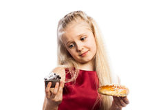 Girl making a choice between two cakes Royalty Free Stock Photography