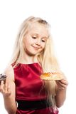 Girl making a choice between two cakes Stock Image