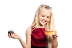 Girl making a choice between two cakes Stock Photography