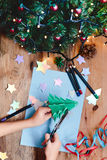 Girl making Christmas tree decoration from paper Stock Photo