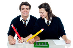 Girl making corrections on her partners paper Stock Photo