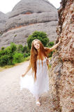 Girl making a dance step. (mountains of Montserrat, Spain stock photography
