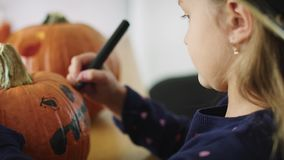Drawing on halloween pumpkin. Girl making decorations for Halloween stock video footage