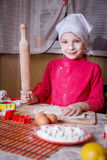Girl making dough with rolling pin Stock Photos